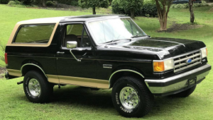 A black and brown ford bronco parked on grass